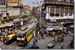A tram winds its way through the streets of Calcutta. Dirty, hot, smoggy, friendly, that's how one resident describes the city, a place so humid even the bulidings seem to sweat. India, 1996.National Geographic, March 1997, India: Fifty Years of Independence.Magnum Photos, NYC5923, MCS1996002 K010.For McCurry, Calcutta is the most visual city on the planet, spinning with chaos and clutter, crumbling under the weight of its overpopulation, utterly out of control, yet vital and alive.  Vendors spill into streets, which hold a confusion of cars, trams, rickshaws, bicycles and pedestrians.  So how to make this picture?  McCurry looked for an office or apartment on a second floor of a street corner.  'And that is the wonder of the place.  Twenty minutes later, I am on a bed in a couple's apartment, making the picture and staying on for a cup of tea.'-Anthony BannonPhaidon, 55, South Southeast, Iconic Images, final book_iconic   A tram winds its way through the streets of Calcutta.  Dirty, hot, smoggy, friendly, it is a place so humid that even the buildings seem to sweat.      For McCurry, Calcutta is the most visual city on the planet, spinning with chaos and clutter, crumbling under the weight of its overpopulation, utterly out of control, yet vital and alive. Vendors spill into streets, which hold a confusion of cars, trams, rickshaws, bicycles and pedestrians. So how to make this picture? McCurry looked for an office or apartment on a second floor of a street corner. 'And that is the wonder of the place. Twenty minutes later, I am on a bed in a couple's apartment, making the picture and staying on for a cup of tea.'