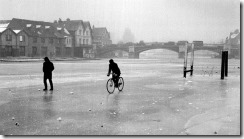 People cycle and walk along a frozen River Thames in London. Credit PA