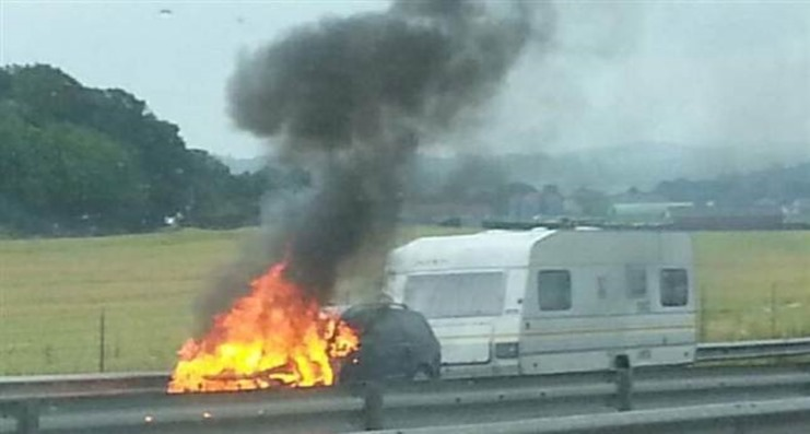 Bil med husvagn fattade eld på E6