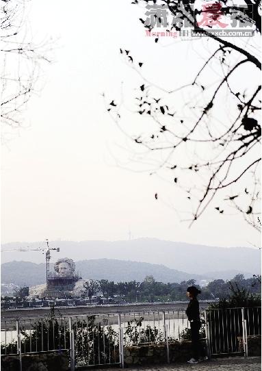 11月1日下午,市民从沿江风光带经过。远处橘子洲头的毛泽东雕像已经雏形初现。图/记者赵尚渝