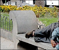 Un  indigente  duerme en un banco de piedra del parque de San Telmo.