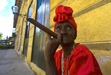 """Cuban Virtudes smokes her Havana cigar in a street of Havana on February 23, 2008. Cuba's National Assembly was to select Sunday a successor to Fidel Castro, likely his brother Raul Castro, extending the Americas' only communist one-party regime in defiance of US-led calls for political opening.Fidel Castro lashed out at Western appeals for democracy in the days leading up to the vote, which will trigger some readjustments in the political chessboard even as the transition bears the exiting leader's imprint.Saturday, Fidel Castro wrote in another editorial that he was eagerly awaiting the """"transcendental decision"""" of the National Assembly, and took a potshot at the US-based Organization of American States which does not allow Cuba to be a member due to its lack of democracy. AFP PHOTO LUIS ACOSTA (Photo credit should read LUIS ACOSTA/AFP/Getty Images)"""