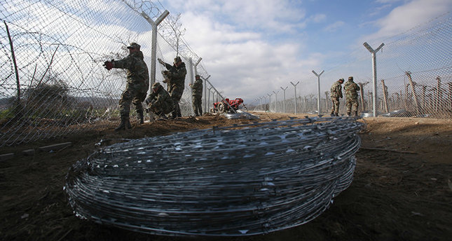 Macedonian army soldiers erect a second fence on the border line with Greece, near the southern Macedonia's town of Gevgelija, Monday, Feb. 8, 2016. Macedonia started reinforcing the border fence with Greece, doubling it with another fence, which is expected to increase the control of the migrant flow. European Union nations anxious to stem the flow of asylum-seekers coming through the Balkans are increasingly considering sending more help to non-member Macedonia as a better way to protect European borders instead of relying on EU member Greece. (AP Photo/Boris Grdanoski)